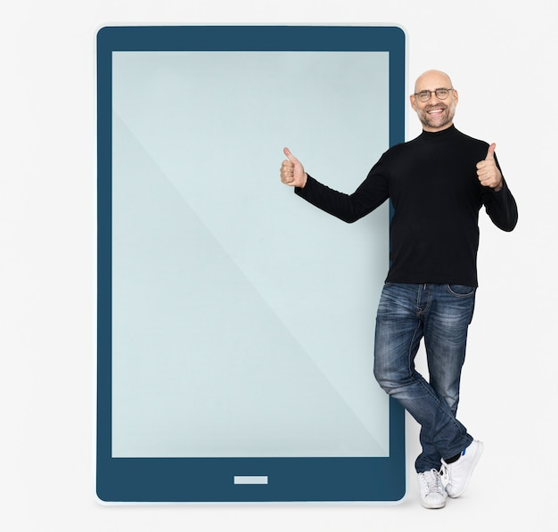 Cheerful man standing beside a tablet