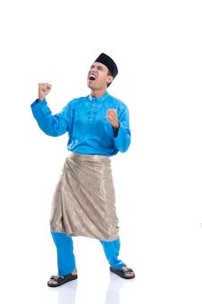 陽気な男の成功。イスラム教徒の服と白い背景の上の腕を上げたアジア人男性