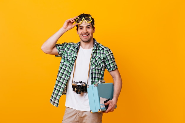 Cheerful man in summer outfit removes his diving mask on orange space. tourist posing with retro camera and blue suitcase.