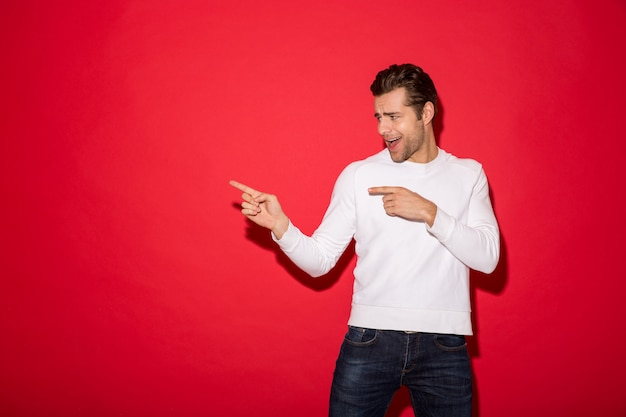 Cheerful man in sweater pointing and looking away with open mouth over red wall