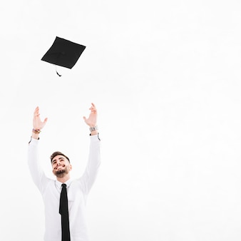 Cheerful man throwing mortarboard