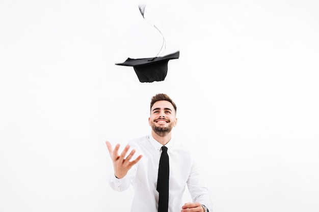 Cheerful man throwing up academic cap