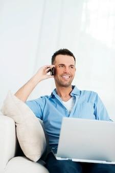 ノートパソコンを使用して携帯電話で話している陽気な男
