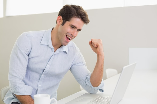 Cheerful man using laptop at home