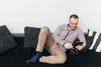 Cheerful man watching film on tablet