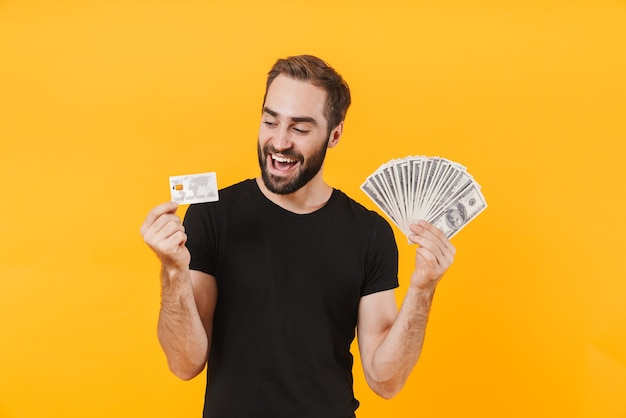 Cheerful man wearing basic black t-shirt holding money cash and credit card isolated over yellow wall