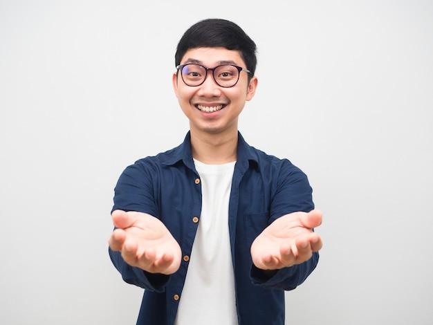眼鏡をかけている陽気な男は、白い背景の何かを保持するために空の手を示す笑顔の顔