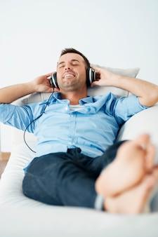 Uomo allegro che indossa le cuffie sdraiato sul divano