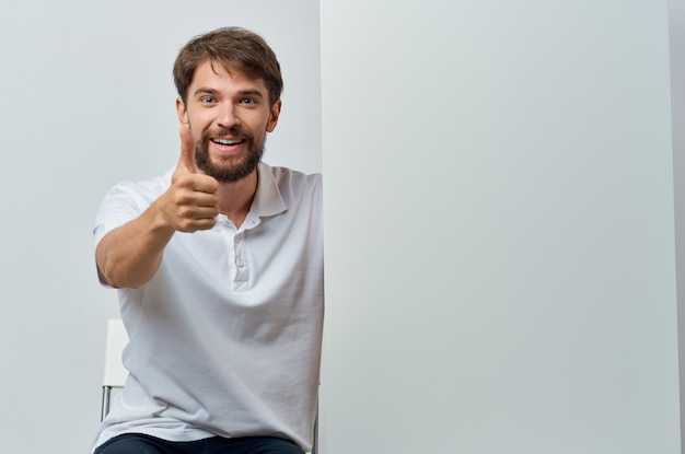 Cheerful man white banner in hand blank sheet presentation isolated background