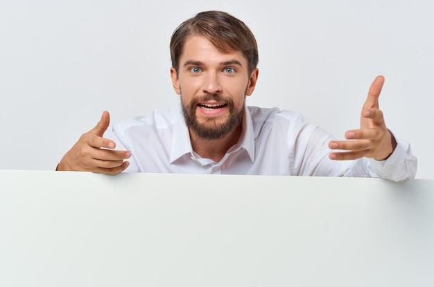 陽気な男の白いバナーを手に空白のシートのプレゼンテーション孤立した背景
