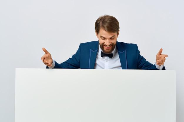 孤立した背景のマーケティングの手に陽気な男の白い紙