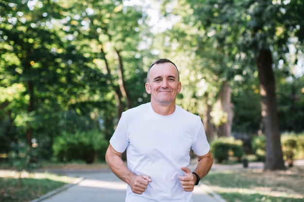 Cheerful man in white tshirt running in a park