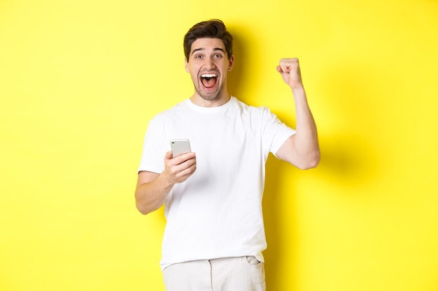 Веселый человек выигрывает на смартфоне, поднимает руку и держит мобильный, достигает цели приложения, стоя