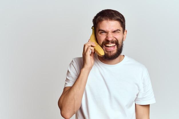 Веселый мужчина с бананом в руках Premium Фотографии