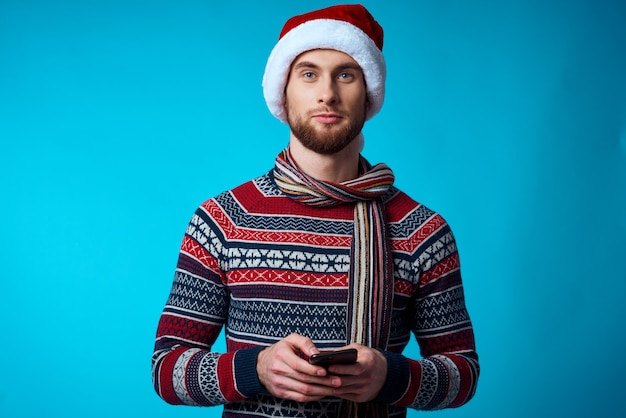 手に携帯電話を持つ陽気な男休日クリスマステクノロジー青い背景