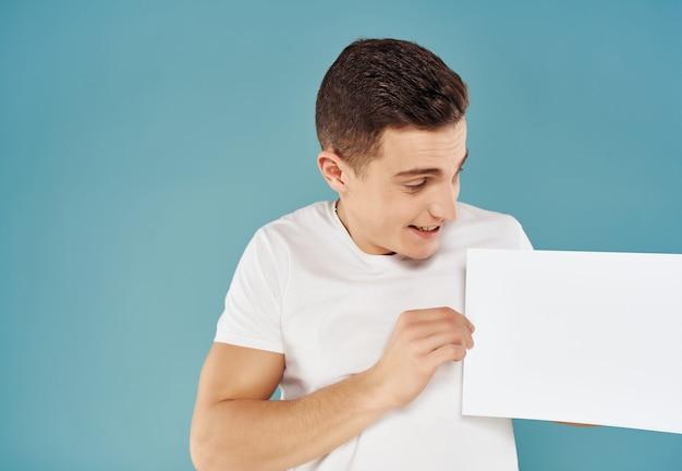 彼の手に一枚の紙を持つ陽気な男は、スペースの感情の青い背景をコピーします