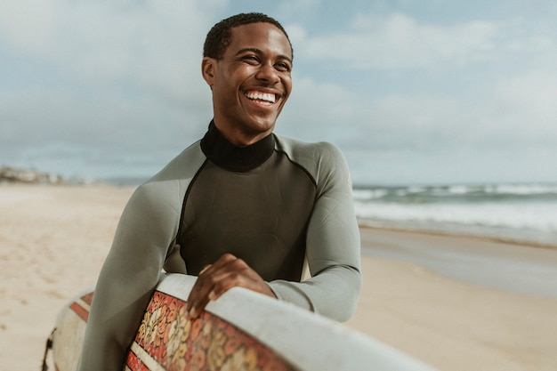ビーチでサーフボードを持つ陽気な男
