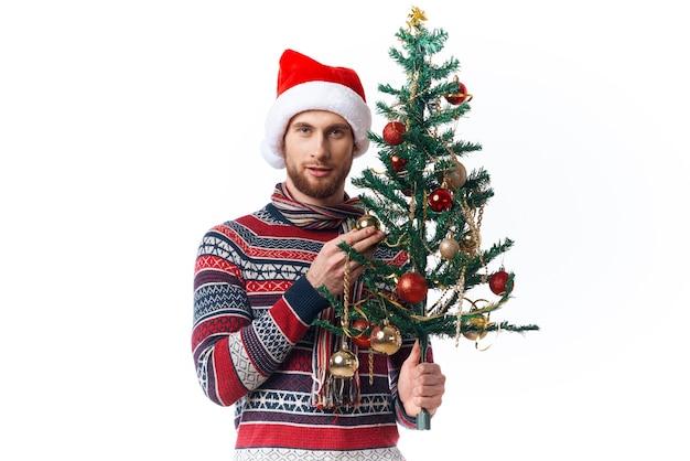 彼の手に木を持つ陽気な男は、休日の楽しみの孤立した背景を飾ります。高品質の写真