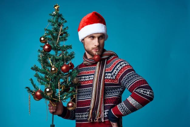 그의 손에 나무와 쾌활 한 남자 장식품 휴일 재미 빨간색 배경