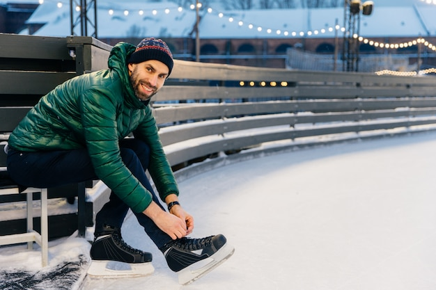 Cheerful man with appealing appearance laces up skates, sitts on ice arena, wants to go skating with friends