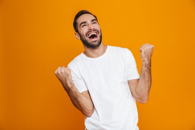 Веселый мужчина с бородой и усами, сжимая кулаки от радости, стоя, изолированный на желтом