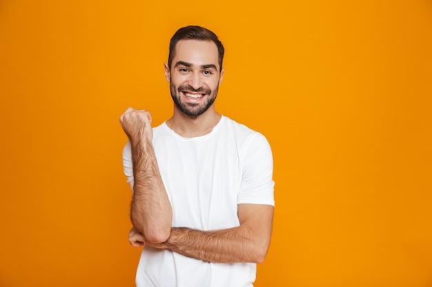 Веселый мужчина с бородой и усами улыбается стоя, изолированный на желтом
