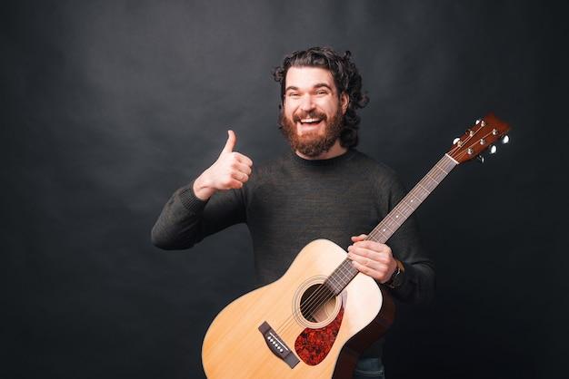엄지 손가락을 보이고 어쿠스틱 기타를 들고 수염을 가진 쾌활한 남자