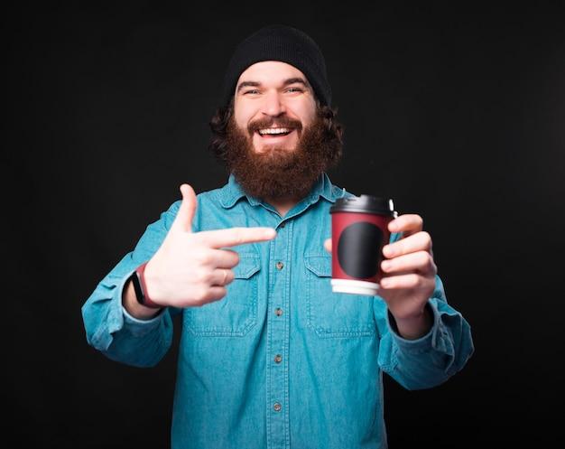 어두운 배경 위에 서서 커피 한잔 빼앗아 가리키는 수염을 가진 쾌활한 남자 프리미엄 사진