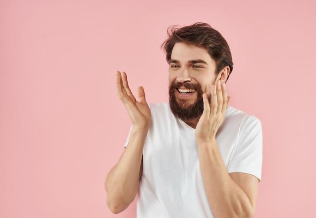 白いtシャツピンクの背景とひげを持つ陽気な男
