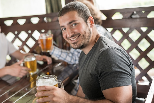 カメラを見てビールと陽気な男