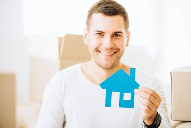 Cheerful man with blue house in hands