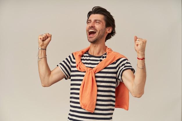 Uomo allegro con capelli castani e setole. indossare t-shirt a righe, maglione annodato sulle spalle. ha braccialetti. alza i pugni, celebra una vittoria