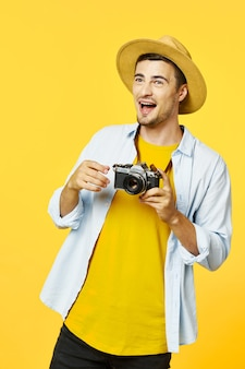 Cheerful man with camera and summer hat