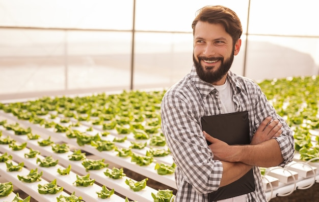 Cheerful man with clipboard smiling and looking away while leaning on hydroponic table during work in hothouse