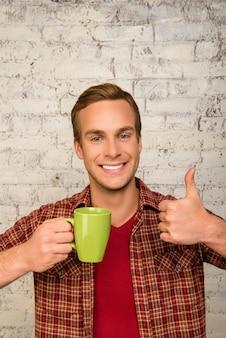 Веселый человек с чашкой чая показывает палец вверх