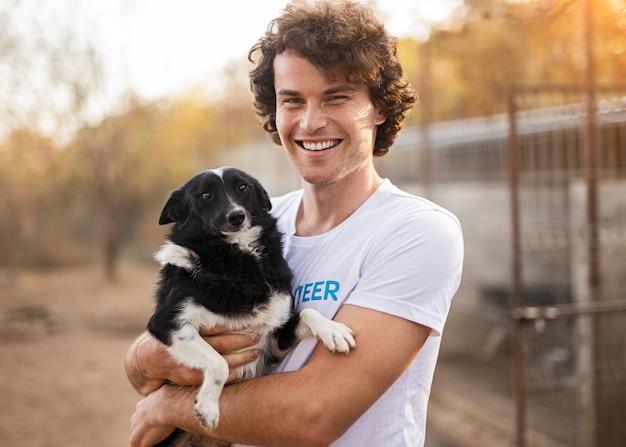 動物保護施設の庭に立っている間、カメラに微笑んで、ホームレスの犬を抱きしめる巻き毛の陽気な男