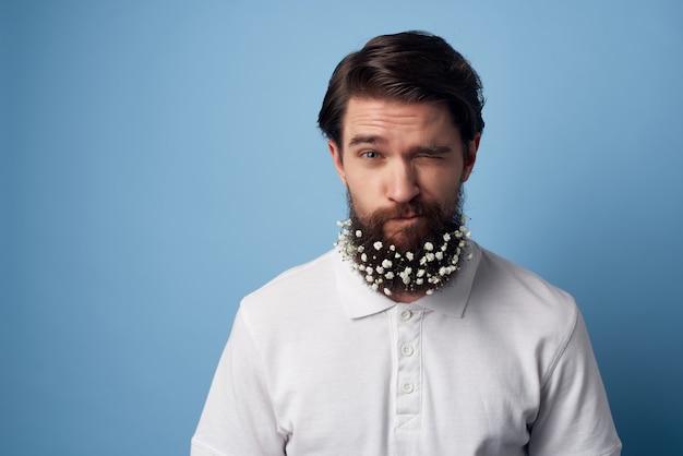 ひげの装飾の白いシャツ青い背景の花と陽気な男