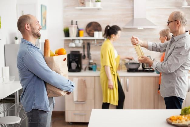 Веселый человек с сумкой для продуктов из супермаркета на домашней кухне. старший мужчина держит бутылку вина.