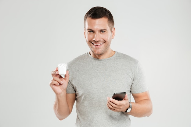 Cheerful man with mobile phone holding earphones.