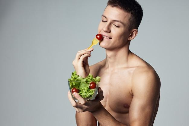健康食品のトリミングされたビューを食べる筋肉の胴体野菜サラダと陽気な男
