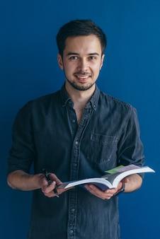 책을 손에 든 쾌활한 남자는 캐주얼하게 옷을 입고 행복하게 웃고 있습니다.