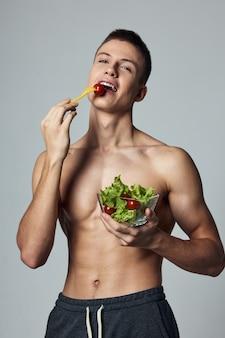 腹筋をポンプでくみ上げた陽気な男は、健康的な食事の食物摂取菜食主義のビタミンを食べます。