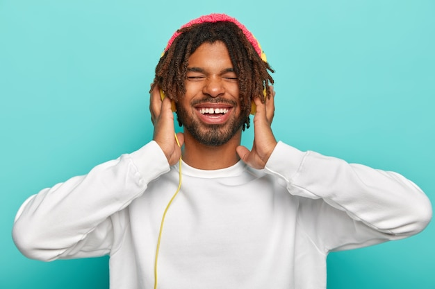 Cheerful man with satisfied expression, enjoys good quality sound in new headphones, keeps eyes shut, listens loud song, smiles broadly