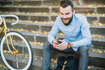 Cheerful man with smartphone sitting near bicycle