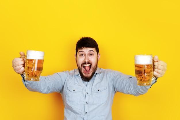 맥주 두 잔을 가진 쾌활한 남자, 트렌디 한 노란색 벽 위에 이미지
