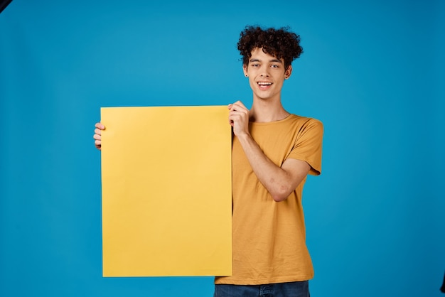 黄色のポスターモックアップ青い背景スタジオを持つ陽気な男。高品質の写真
