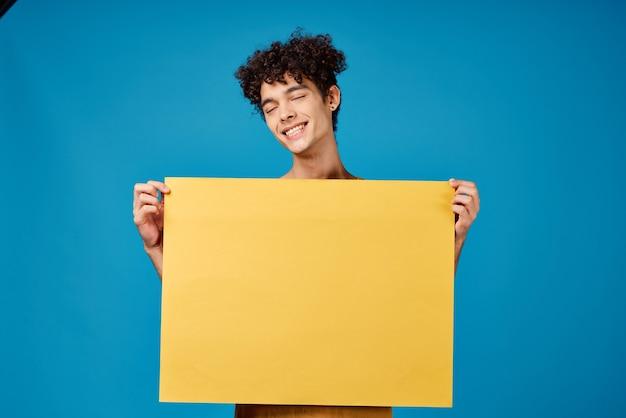 Веселый человек с желтым постером макет синем фоне студия
