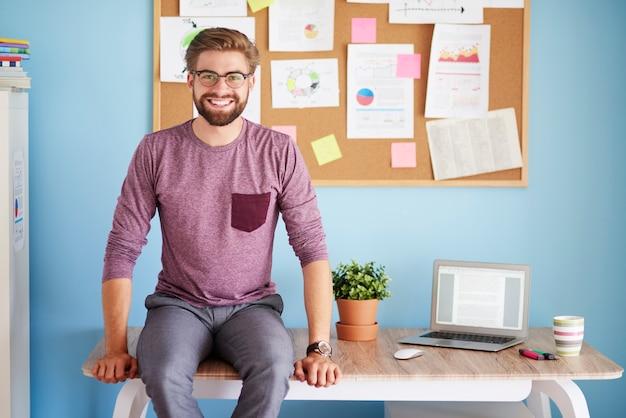 Веселый человек, сидящий на офисном столе