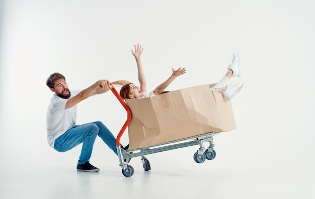 Cheerful man and woman in a box on a cargo trolley emotions light background model