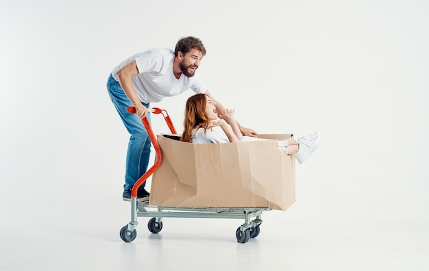 Cheerful man and woman in a box on a cargo trolley emotions light space model